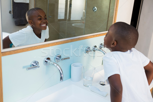 High angle view of boy clenching teeth while looking at mirror Stock photo © wavebreak_media