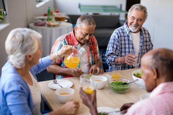 Senior female serving drink to male friends Stock photo © wavebreak_media