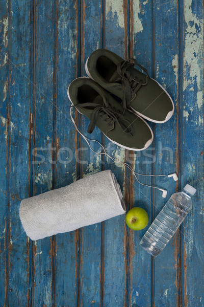 Directly above view of sports shoes and napkin by headphones with water bottle on table Stock photo © wavebreak_media