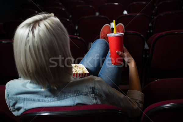 Rear view of woman having drinks while watching movie in theatre Stock photo © wavebreak_media