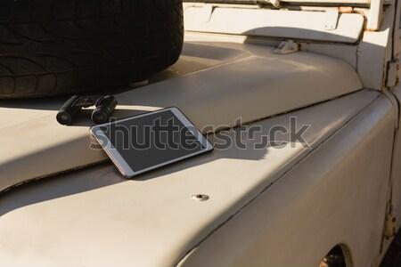 Tablet and binocular on vehicle hood Stock photo © wavebreak_media
