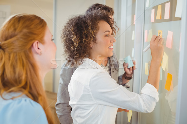Stock photo: Businesswoman writing on glass as colleagues looking at it