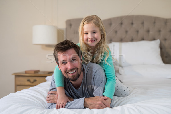 Father and daughter having fun on bed Stock photo © wavebreak_media