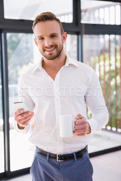 Sorridente homem caneca sala de estar telefone Foto stock © wavebreak_media