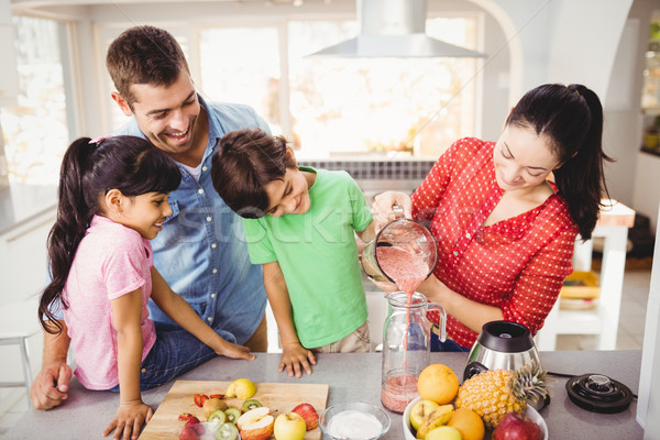 Smiling family with mother pouring fruit juice  Stock photo © wavebreak_media
