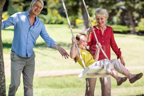 Nonni spingendo pronipote swing parco donna Foto d'archivio © wavebreak_media