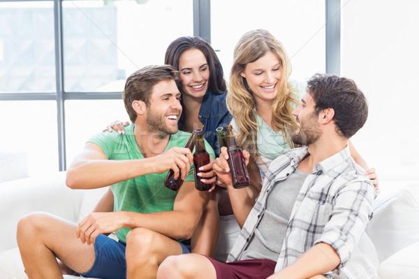 Sorridente amigos sessão sofá potável mulher Foto stock © wavebreak_media