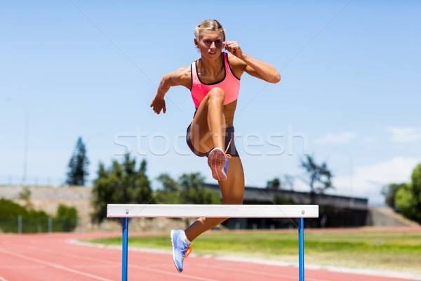 Female athlete jumping above the hurdle Stock photo © wavebreak_media