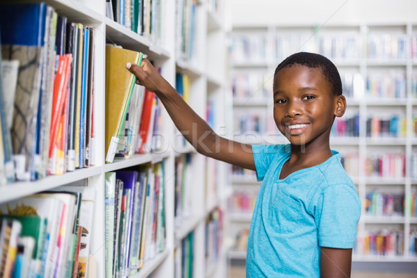 Schoolboy selecting a book from bookcase in library Stock photo © wavebreak_media