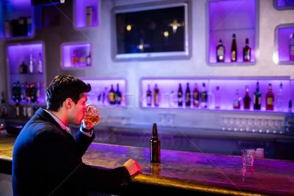 Człowiek pitnej alkoholu bar Licznik butelki Zdjęcia stock © wavebreak_media