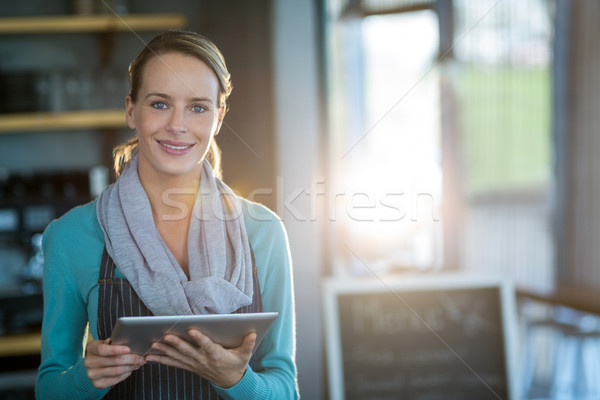 Stock photo: Smiling waitress using digital tablet in cafe