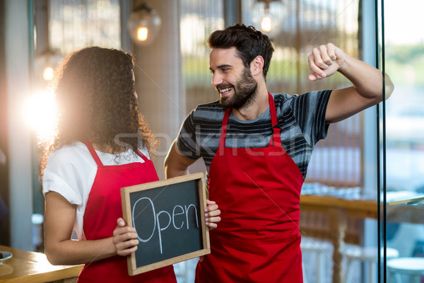 Waitress and waiter standing with open sign board in cafe Stock photo © wavebreak_media