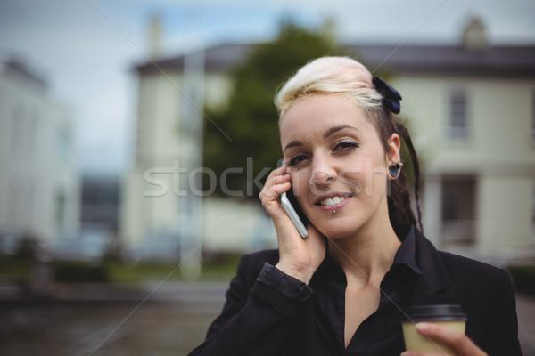 Retrato mujer de negocios hablar teléfono móvil desechable Foto stock © wavebreak_media