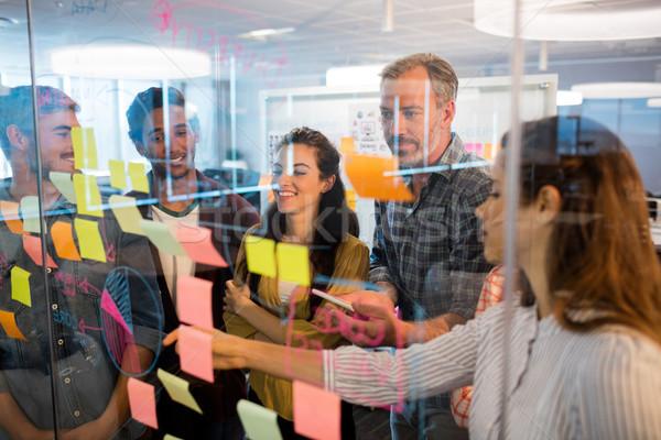 Creativa equipo de negocios mirando notas adhesivas vidrio ventana Foto stock © wavebreak_media