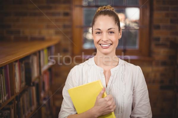 Blonde teacher holding book in the library Stock photo © wavebreak_media