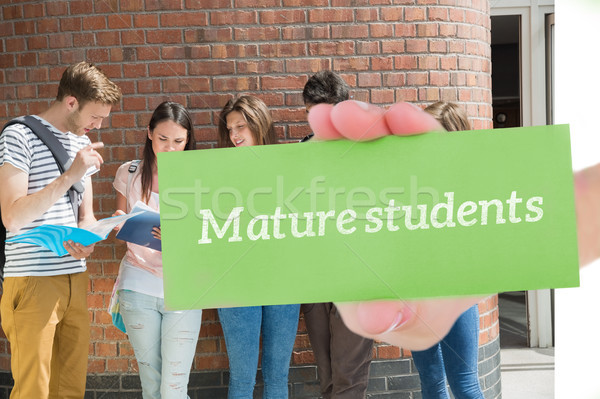 Mature students against happy students standing and reading Stock photo © wavebreak_media