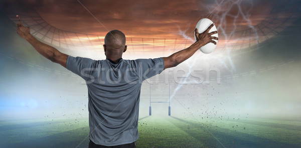 Composite image of rear view of sportsman with arms raised holding rugby ball Stock photo © wavebreak_media