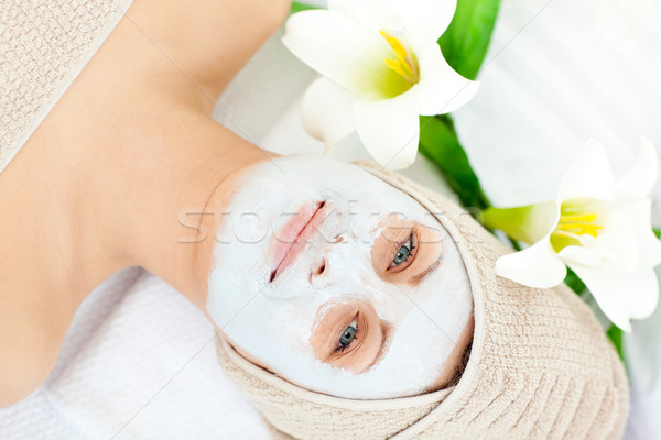 Smiling woman with white cream on her face looking at the camera in a spa center Stock photo © wavebreak_media