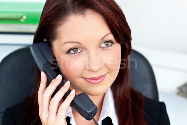 Assertive young businesswoman talking on phone smiling at the camera Stock photo © wavebreak_media