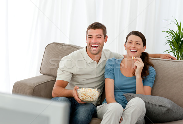 Lovely couple laughing while relaxing in front of the television Stock photo © wavebreak_media