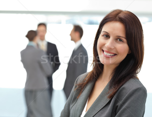 Pretty businesswoman posing in front of her team while working in the background Stock photo © wavebreak_media