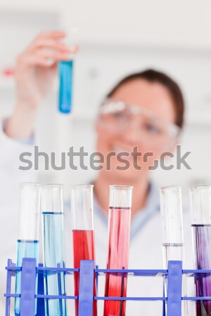 Beautiful female biologist holding a manual pipette with sample from test tubes in a lab Stock photo © wavebreak_media