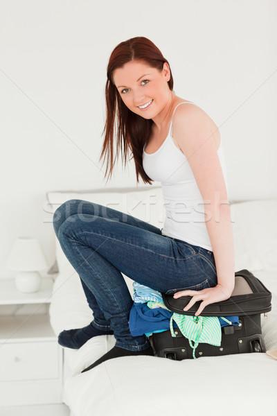 Güzel bir kadın oturma bavul yatak odası yatak çanta Stok fotoğraf © wavebreak_media