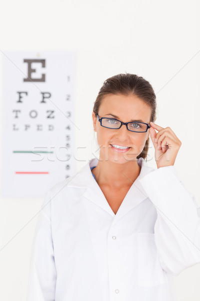 Eye specialist wearing glasses looking into the camera in her surgery Stock photo © wavebreak_media