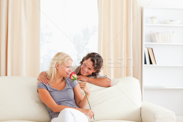 Lovely couple with a flower in their living room Stock photo © wavebreak_media