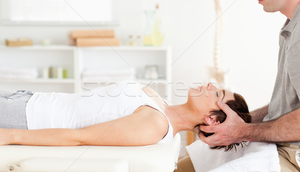 Chiropractor stretching a cute woman in a room Stock photo © wavebreak_media