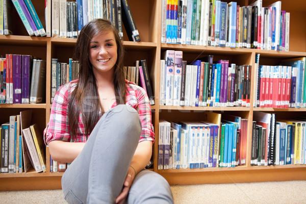 Sonriendo estudiante sesión estantería biblioteca mujer Foto stock © wavebreak_media