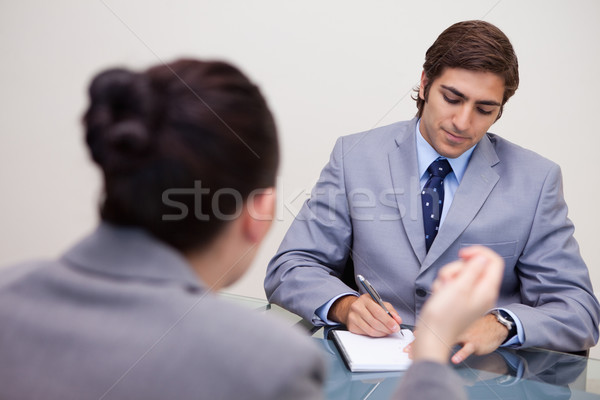 Young businessman in negotiation taking notes Stock photo © wavebreak_media