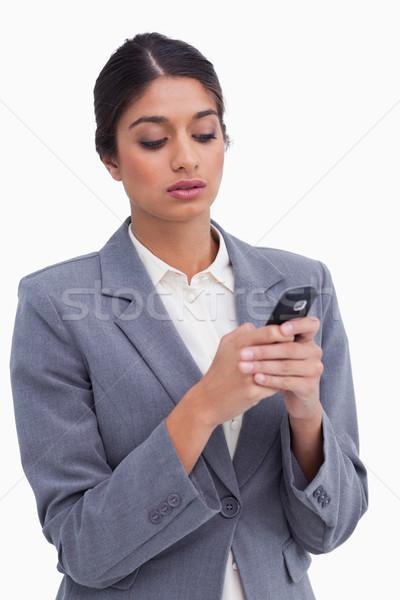 Female entrepreneur writing text message on her cellphone against a white background Stock photo © wavebreak_media