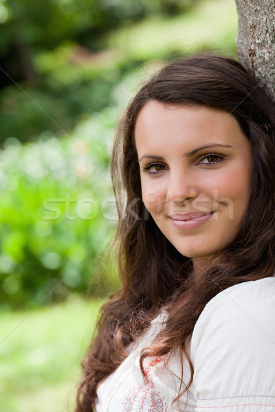 Young calm woman looking at the camera while leaning against a tree in a parkland Stock photo © wavebreak_media
