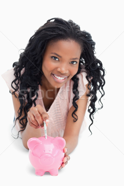 A smiling young girl is looking at the camera and putting money into a piggy bank against a white ba Stock photo © wavebreak_media