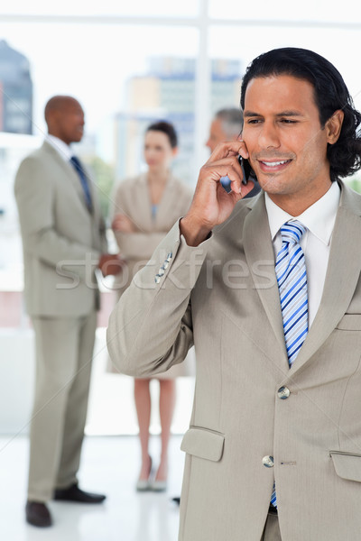 Businessman using a mobile phone while his team are communicating behind him Stock photo © wavebreak_media