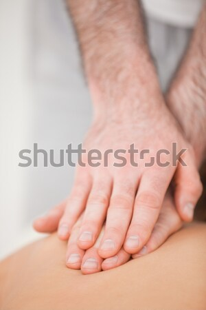 Osteopath massaging his patient while pressing his back in a room Stock photo © wavebreak_media