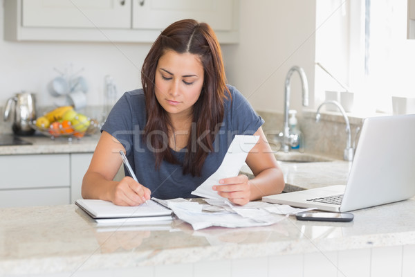 Woman calculating receipts with laptop in kitchen Stock photo © wavebreak_media