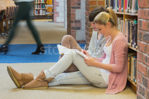 Students sitting in front of a bookshelf in college library studying Stock photo © wavebreak_media