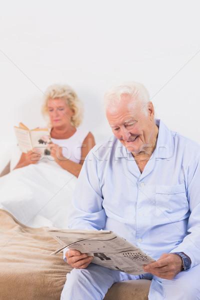 улыбаясь пожилого пару чтение кровать спальня Сток-фото © wavebreak_media