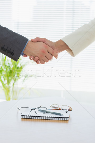 Closeup of shaking hands over eye glasses and diary Stock photo © wavebreak_media