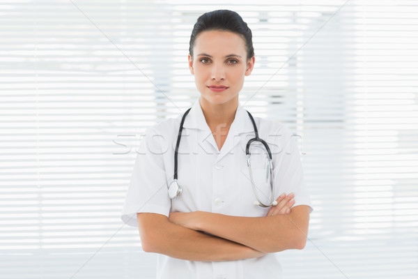 Beautiful female doctor standing with arms crossed Stock photo © wavebreak_media