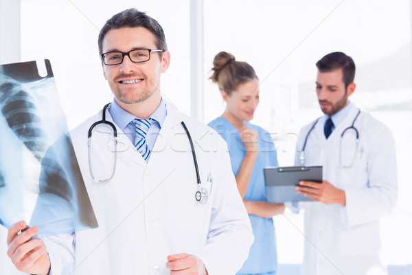 Male doctor examining xray with colleagues behind Stock photo © wavebreak_media