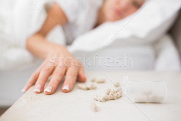 Woman sleeping in bed with pills in foreground Stock photo © wavebreak_media