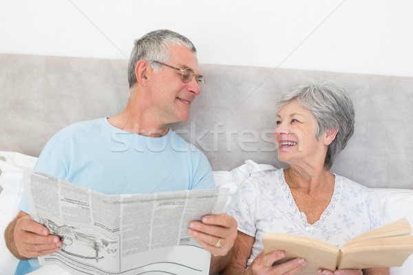 Stock photo: Senior couple with newspaper and book in bed