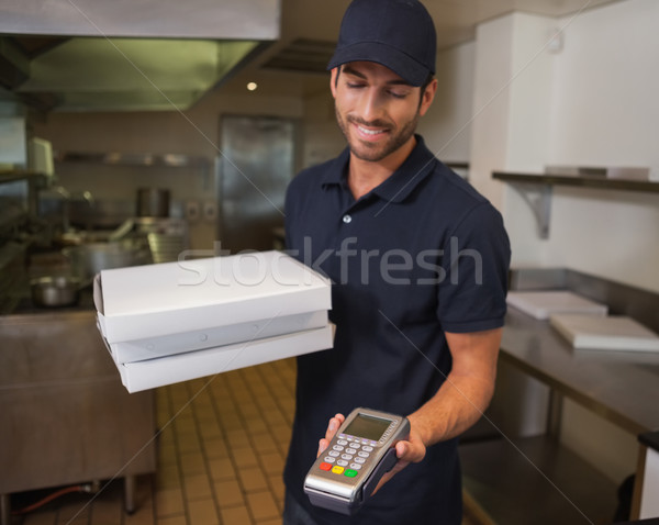 Happy pizza delivery man holding credit card machine Stock photo © wavebreak_media