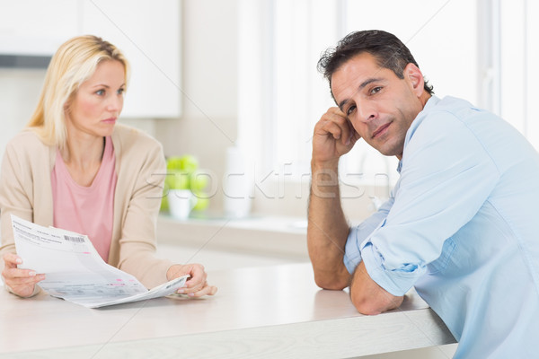Stock photo: Upset couple with newspaper sitting in kitchen