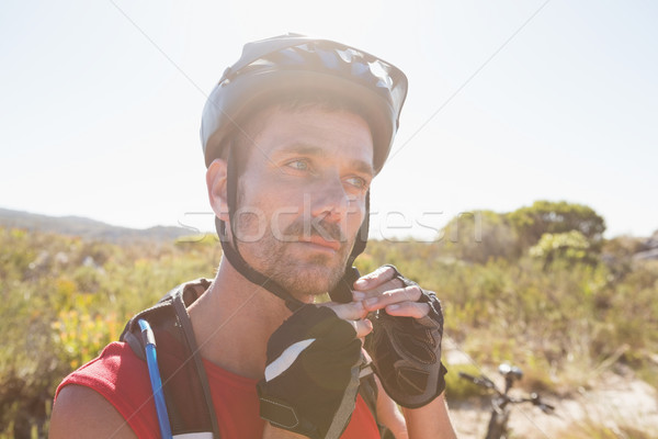 Fit cyclist adjusting helmet strap on country terrain Stock photo © wavebreak_media