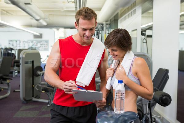 Bello personal trainer client guardando appunti palestra Foto d'archivio © wavebreak_media