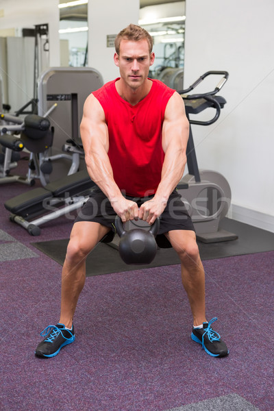Strong man lifting heavy kettlebell Stock photo © wavebreak_media